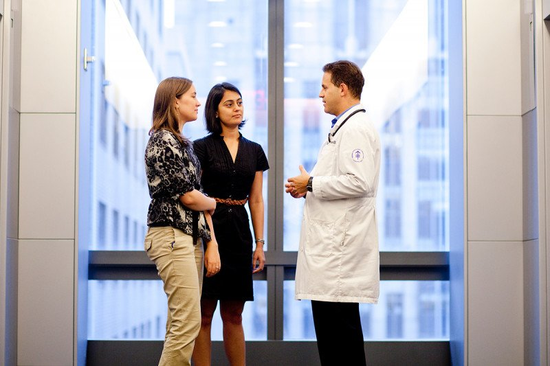 Two GSK students talking to a physician in a hallway.