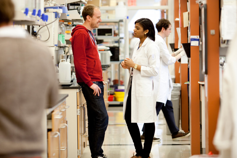 GSK student talking to a researcher in a laboratory.