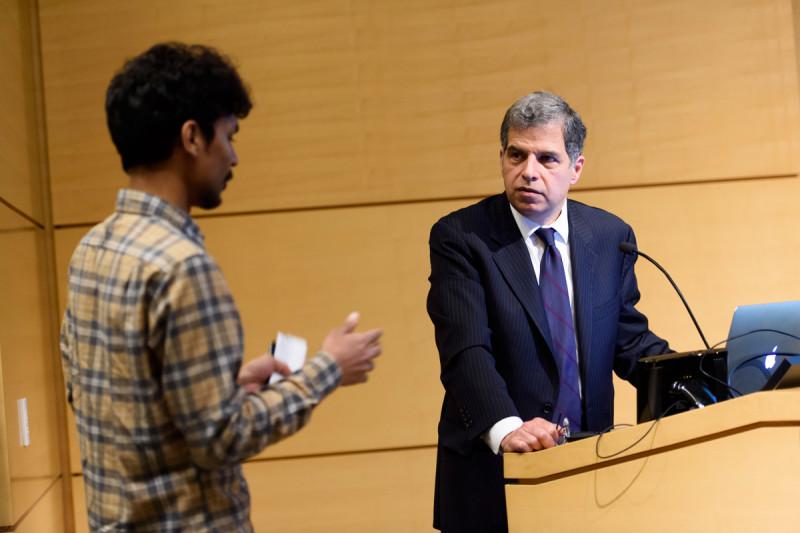GSK student, Nayan Jain, speaks with a symposium presenter, Dr. Gary Schwartz.