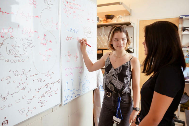 Two women look at a whiteboard
