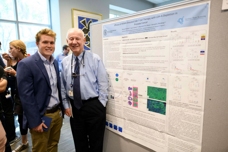 Two men pose in front of scientific poster